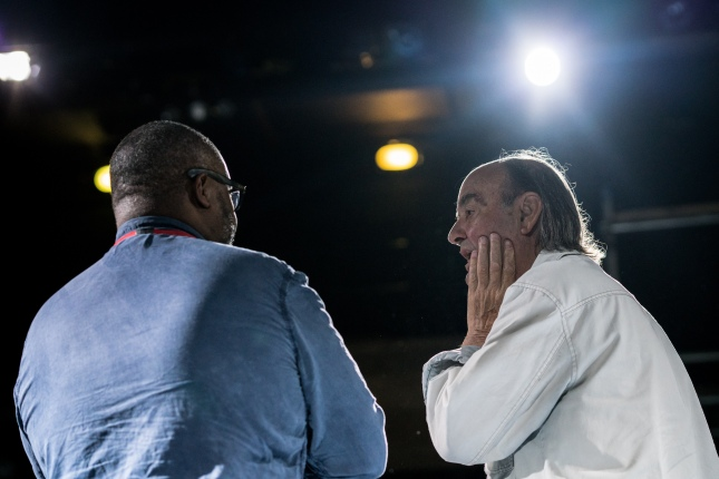 An actor from Life of Galileo is talking to an audience member, who listens with a look of rapt attention, his hand up to his mouth, his mouth open. The two men have their backs to us but their heads are turned inwards, towards each other, so that we can see their expressions. A stage light shines brightly in the background, out of focus.