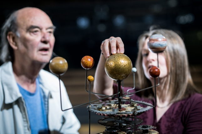 An audience member listens to the Life of Galileo stage manager describe a heliocentric model of the solar system prop from the show. The audience member and stage manager are in the background of the image with the focus on the heliocentric model of the solar system in the foreground with the stage manager's hand placed on the sun.